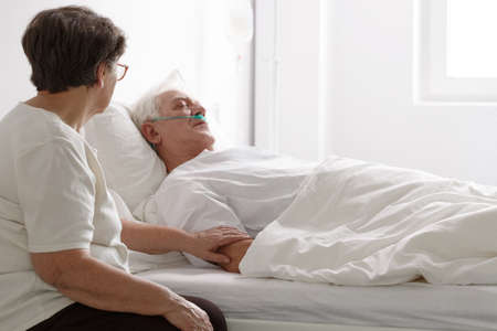 Senior man in a coma laying on hospital bed and his wife sitting next to him
