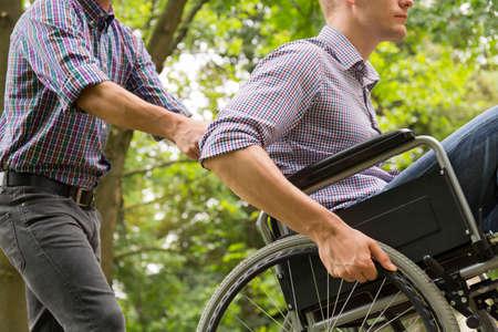 휠체어에 그의 친구를 밀고 남자의 총