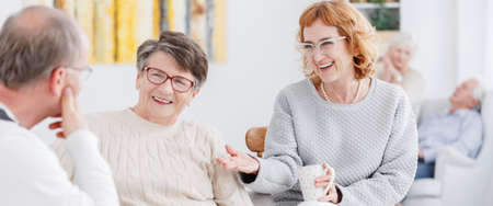 Two happy senior women talking to a man with glasses