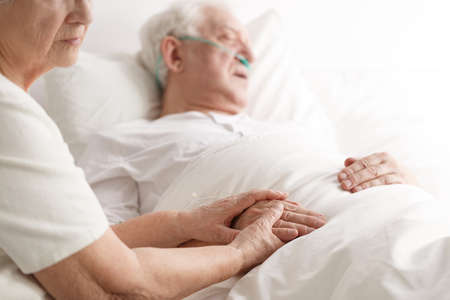 Dying senior man laying on a bed and his wife holding his hand Stock Photo