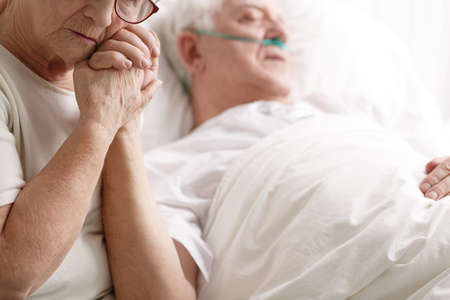 Dying senior man in hospital bed and his sad wife holding his hand