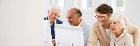 Positive older woman helping her senior friend using computer