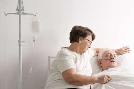 年配の女性がホスピスで彼女の病気の夫の世話 写真素材