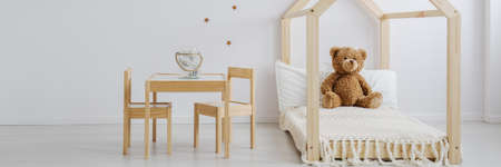 Neutral baby room with wooden furniture set and wall stickers