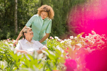 Senior woman on a wheelchair and looking at her young nurse, surrounded by flowers