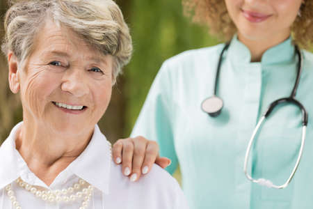 Close shot of elderly, smiling woman with the doctors hand on senior shoulder