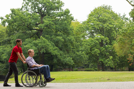 Young man pushing disabled person on wheelchair in the park