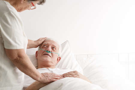 Sick senior man laying on a bed and his wife standing next to him in hospice