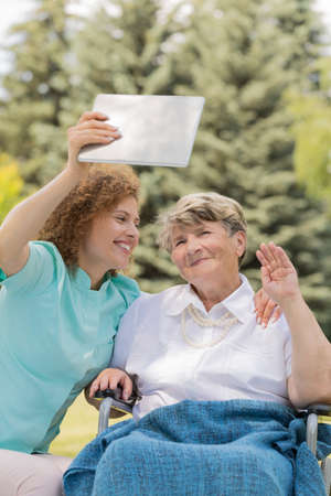 Young nurse sitting close to older woman on a wheelchair and taking selfie by tablet