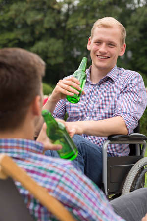 Positive man on wheelchair drinking beer with his friend Stock Photo
