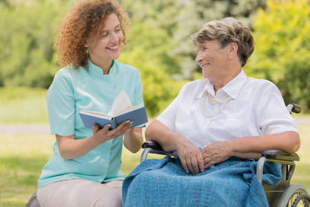Young nurse sitting close to the elderly woman on a wheelchair and reading her a book in a garden