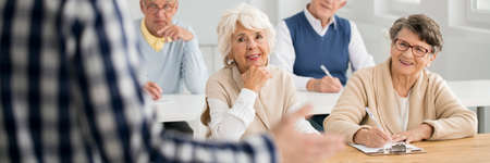 Senior women looking flirtatiously at male teacher during lecture Stock Photo