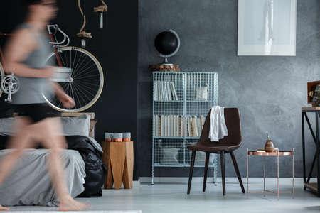 furniture design: Man walking trough his black and grey bedroom