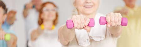 Activo mujer senior de formación con pesas en el gimnasio Foto de archivo