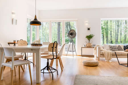Dining space with wooden table in cozy modern lounge Reklamní fotografie
