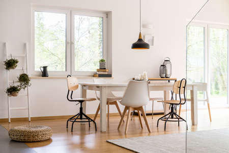 White modern dining hall with big table and designer chairs