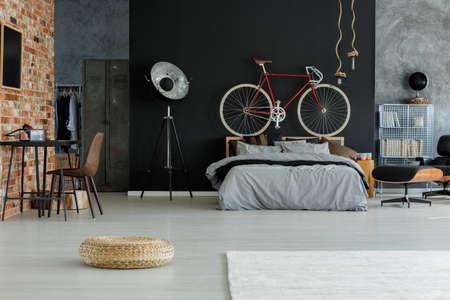 Quarto espaçoso com design elegante e bicicleta vermelha em cima da cama Foto de archivo - 82322632