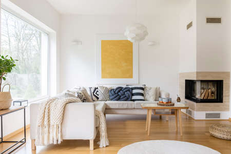 Witte bank met kussens en moderne open haard in stijlvolle woonkamer Stockfoto