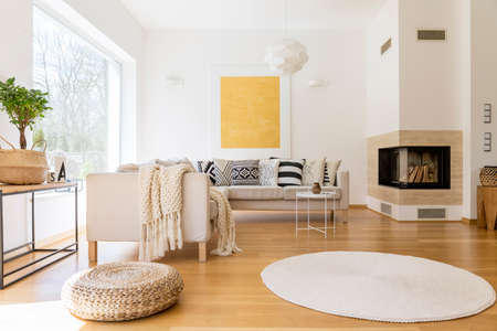 Ruime witte en houten woonkamer met moderne open haard en een bank