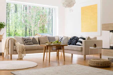 편안한 소파와 나무 커피 테이블이있는 아늑한 흰색 거실 스톡 콘텐츠