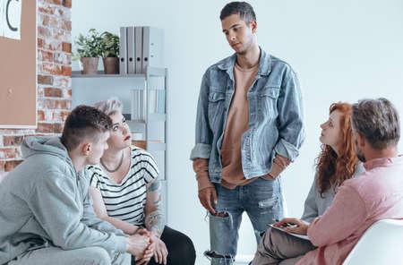 Tiener spreekt aan een groep tijdgenoten op therapie sessie Stockfoto