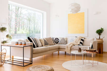 Modern interior of spacious lounge with sofa and three coffee tables