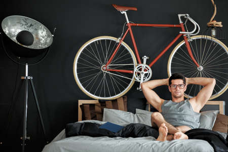 furniture design: Red bike on a black wall in modern decorated bedroom