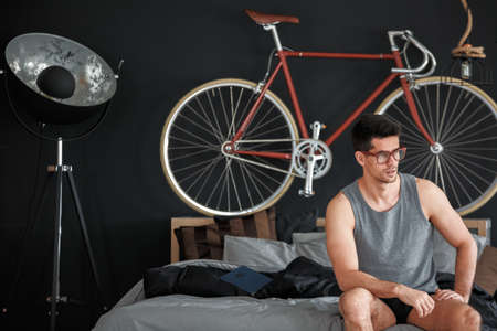 furniture design: Muscular young man sitting on a wooden bed in bedroom