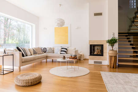 Stylish white living room with wooden stairs to the first floor