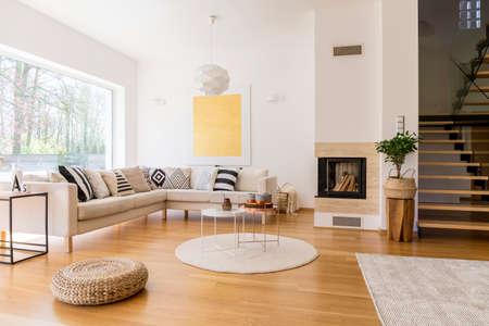 Stijlvolle witte woonkamer met houten trap naar de eerste verdieping