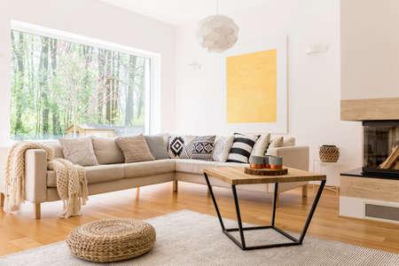 Houten salontafel en witte bank in gezellige trendy ontworpen woonkamer