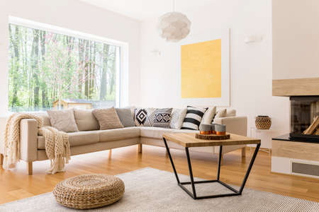 Wooden coffee table and white sofa in cozy trendy designed living room