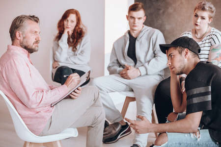 Insightful therapist talking to a troubled teenager, psychotherapy concept Stock Photo