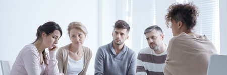 Scared woman suffering from anxiety disorder during group therapy Stock Photo