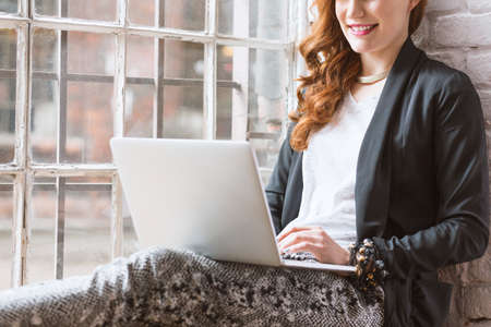 owning: Female freelancer working on computer by the window in home Stock Photo