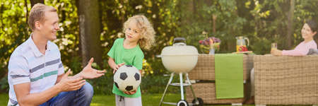 Man and boy with ball during family grill in the garden