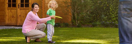 Mother and son playing frisbee during family afternoon in the garden Stock Photo