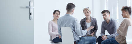 Distressed young man confiding to his supporting psychotherapy group Stock Photo - 82347483