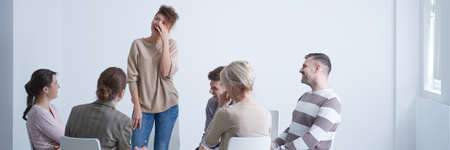 Support group looking at woman crying from strong emotions