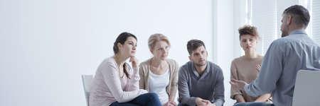 Steungroep die in cirkel zit terwijl de mens zijn problemen vertrouwt Stockfoto