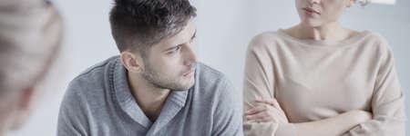 Verstoorde mens die aan echtelijke therapeut met zijn boze vrouw opzij luistert