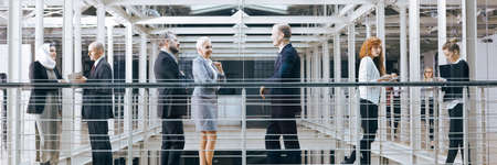 large group of business people: Group of business people talking in modern interior, panorama