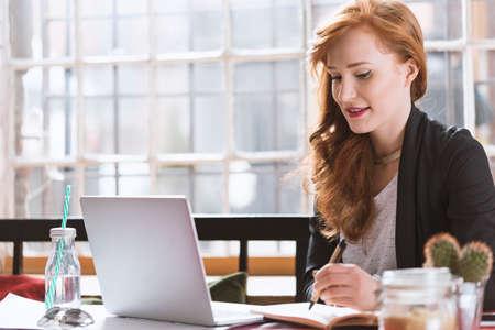 大きな窓のあるカフェでコンピュータで勉強するジンジャー女性