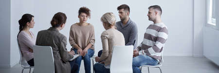 People are helping their female friend during group psychotherapy Stock Photo