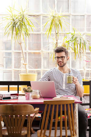 Smiling young architect working in industrial style office with laptop Stok Fotoğraf