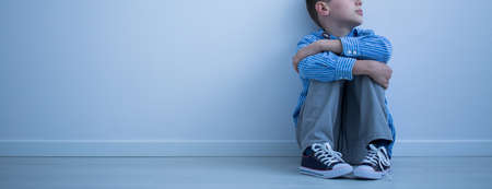 Child sitting on the floor in an empty room Stock Photo