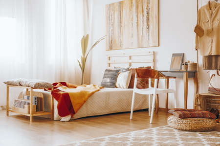Wooden bed with blanket and pillows standing in cozy bedroom in sandy colors