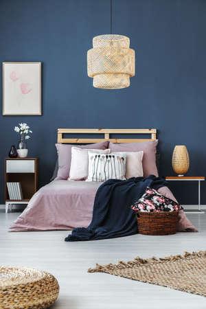 Dark blue blanket thrown on the bed with bright stylish bedding Standard-Bild
