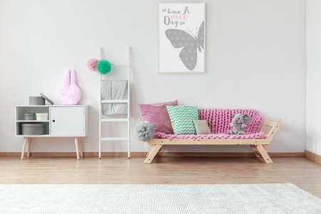 아이 방에 흰 사다리 옆에 나무 소파에 핑크색 담요