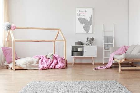 Gemütliches Baby mit positiver Plakat eines Schmetterlings auf der Wand Standard-Bild - 82360822
